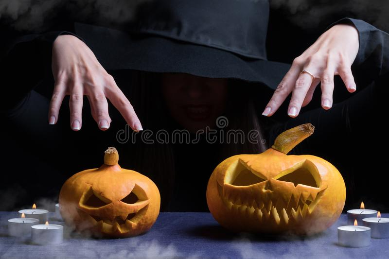 Halloween Witch with a magic Pumpkin. Beautiful young woman in witches hat and costume holding carved pumpkin. Halloween art desig stock images