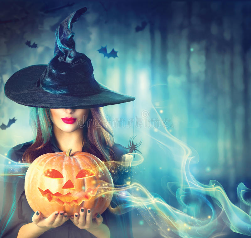 Halloween witch with a magic pumpkin. In a dark forest stock photos