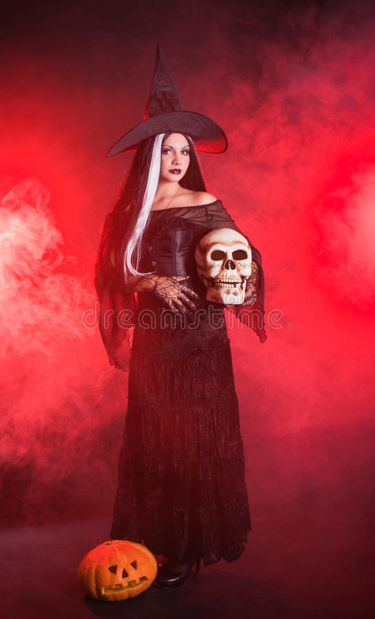 Halloween Witch With A Skull And Pumpkin Royalty Free Stock Image