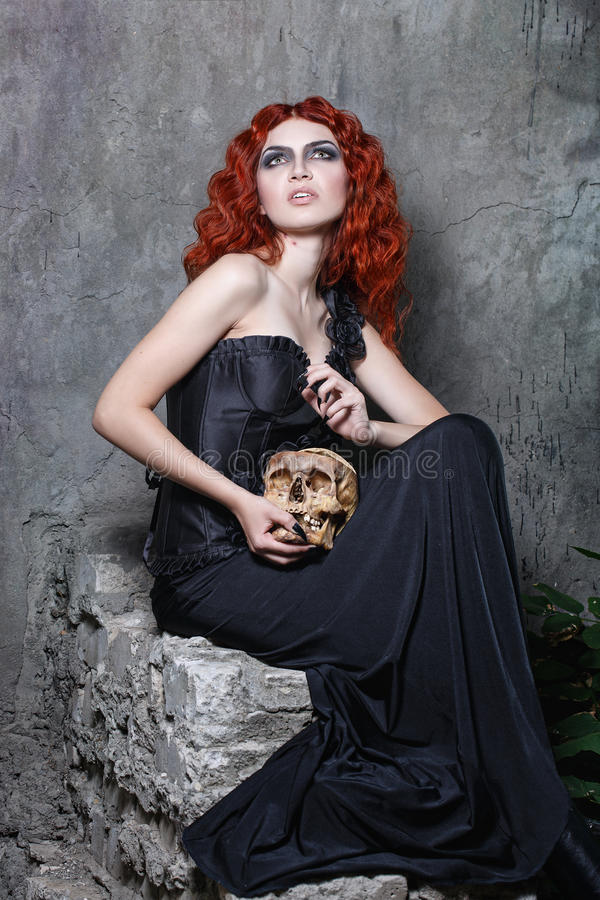 Halloween, witch, vampire, skull. Red-haired vampire girl posing with a skull in her hands in urban twilight stock photo