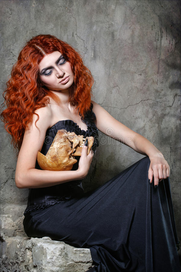 Halloween, witch, vampire, skull. Red-haired vampire girl posing with a skull in her hands in urban twilight stock photography