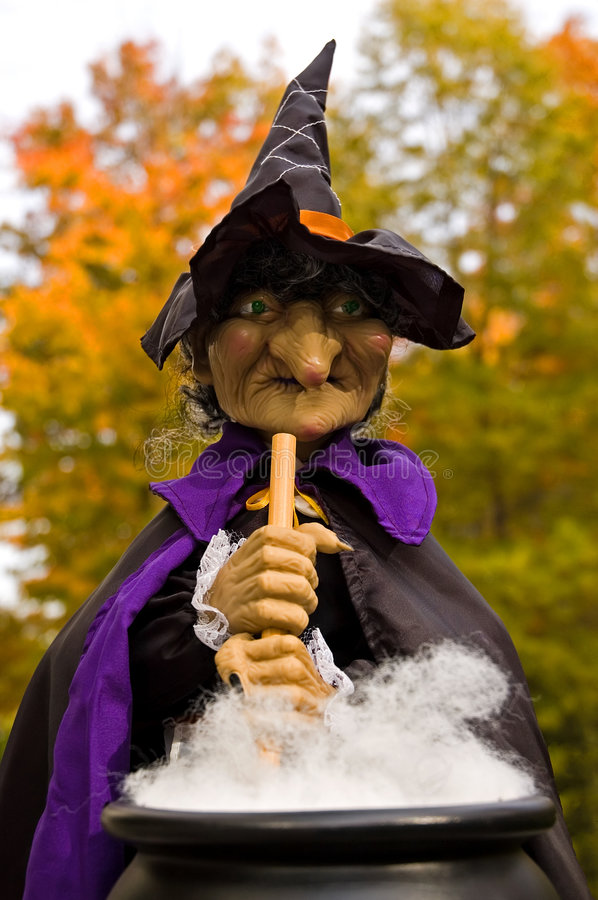Halloween Witches Brew. Halloween figure of a witch stirring a boiling pot of brew stock image