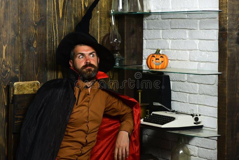 Halloween wizard sitting at pumpkin, typewriter, books on shelves royalty free stock photo