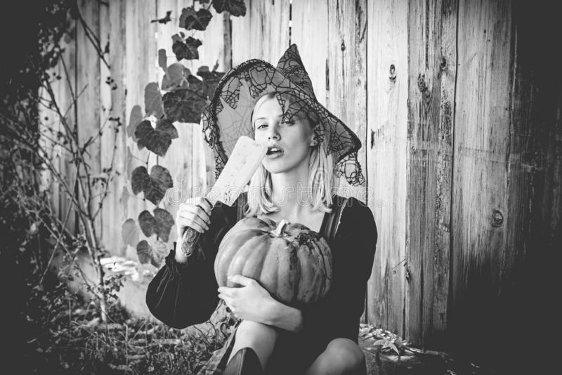 Halloween woman. Attractive witch holding pumpkin and knife for a `trick or treat`. Woman dressing in Halloween costume stock photo