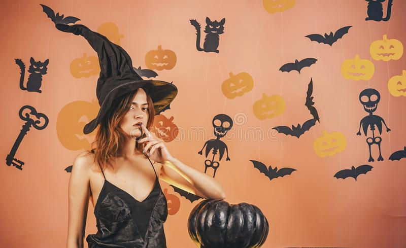 Halloween woman design. Halloween Witch with a carved Pumpkin and magic lights. Sexy Models Posing on Halloween stock photography