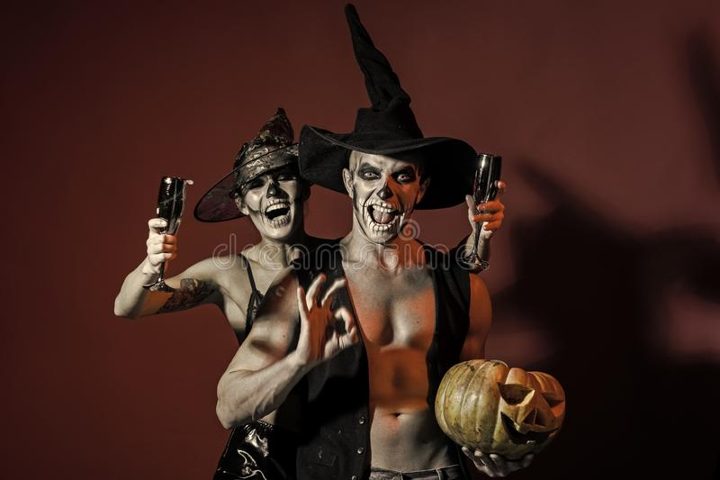 Halloween woman and man has happy face in witch hat. Halloween women and men has happy face in witch hat. Couple in love with pumpkin and wine glass. Holiday royalty free stock photography