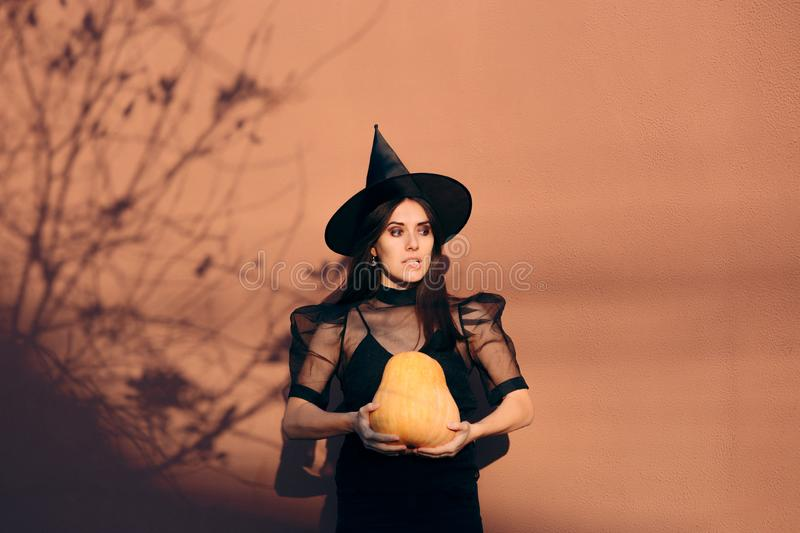 Halloween Woman in Witch Costume Holding Pumpkin stock image