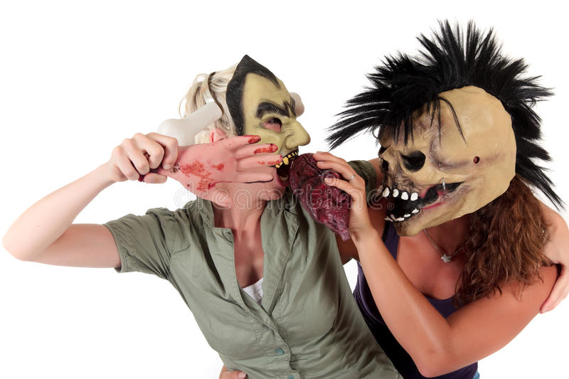 Halloween women masks. Young Halloween women with ugly scary masks, one fighting with a bloody hand against an organ. Studio shot. White background stock photo