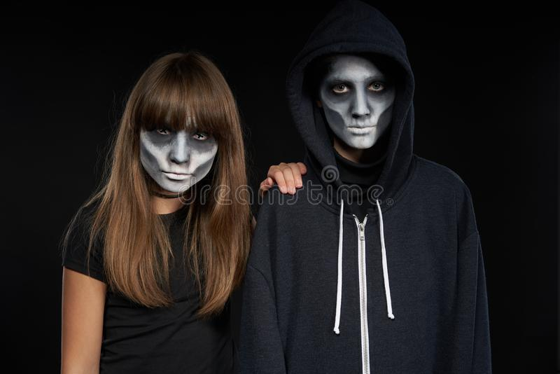 Boy with Halloween zombie makeup with hood on l. Halloween zombie friends. Two preteen kids with zombie makeup looking at camera on black background royalty free stock image