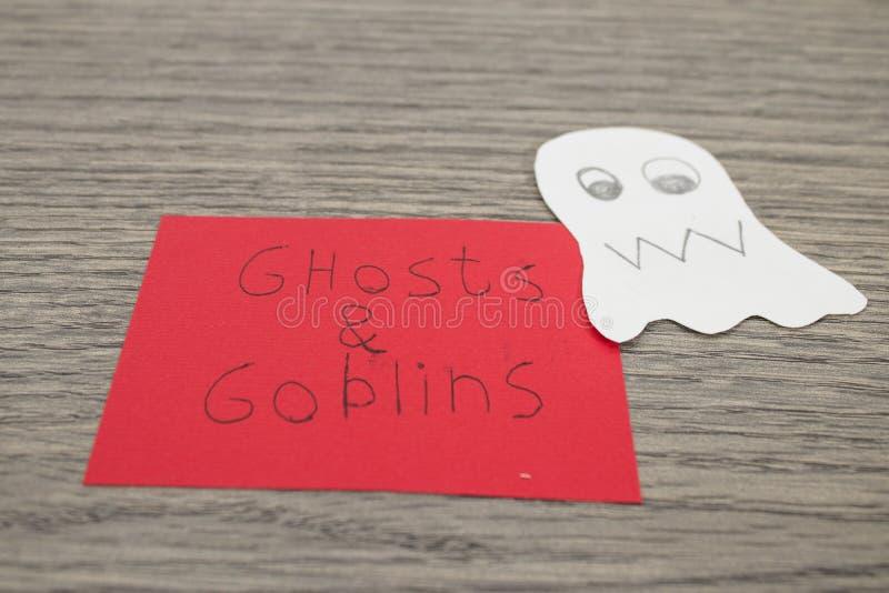 Halloween-Zusammensetzung, -geister und -kobolde handgeschrieben auf einem roten p stockbilder