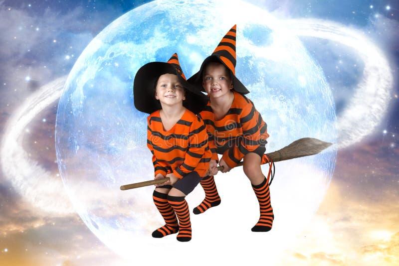 Halloween Zwei der Jungenzaubererfliege auf Besenstiel über dem Himmel Schöne Kinder in Halloween-Kostümen stockbilder