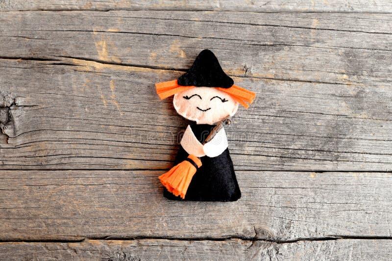 Halloweenowa śliczna odczuwana czarownica z miotłą na starym drewnianym tle krok Odgórny widok zdjęcia stock