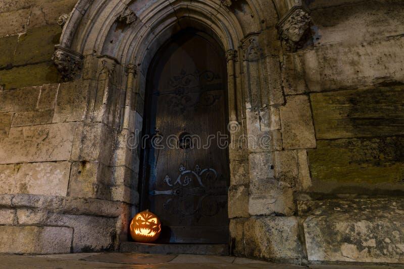 Halloweenowa bania przed antycznym drewnianym drzwi i kamienną ścianą kościół, Niemcy zdjęcie royalty free