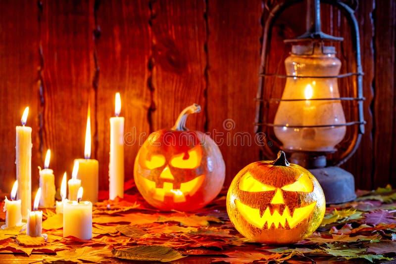 Halloweenowa bania z rozjarzoną twarzą na drewnianym tle z wiele płomiennymi świeczkami, antykwarskim lampionem i jesień liśćmi,  zdjęcia royalty free