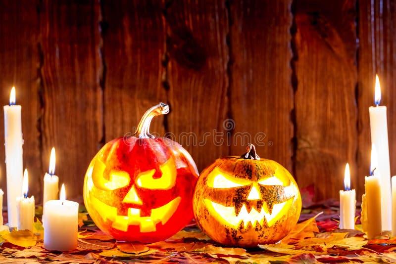 Halloweenowa bania z rozjarzoną twarzą na drewnianym tle z wiele płomiennymi jesień liśćmi i świeczkami Pomysł dla ulotek, plakat obrazy royalty free