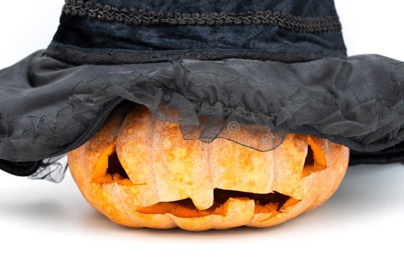 Halloweenowa bania z rzeźbiącą twarzą w czarownica kapeluszu na białym tle Straszna rzeźbiąca bania dla Halloween obrazy royalty free