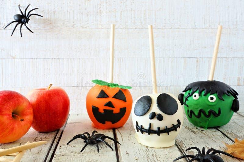 Halloweenowa cukierku jabłka scena przeciw białemu drewnianemu tłu fotografia stock