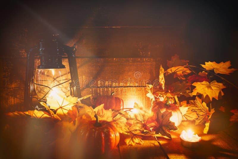 Halloweenowa dyniowa latarniowa świeczka z suchą liść jesienią na drewnianym dekoruje na Halloween tła wakacje z skutkiem fotografia stock