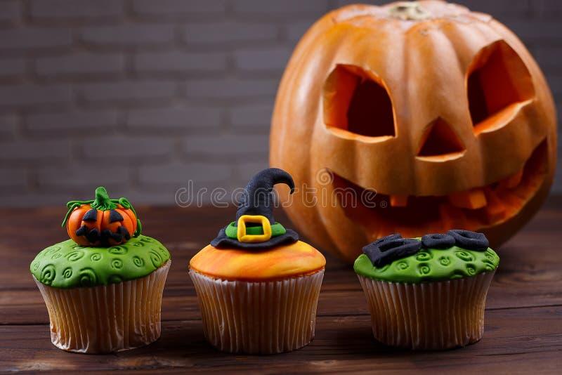 Halloweenowe babeczki z barwionymi dekoracjami: bania h i czarownica fotografia royalty free