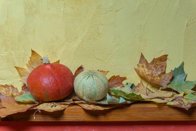 Halloweenowe bani głowy i susi jesień liście na drewnianej desce w przód malującym ściennym tle zdjęcie stock
