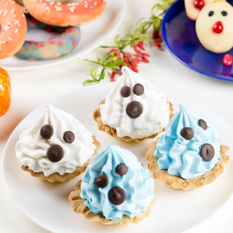 Halloweenowe cukierki fundy, partyjny karmowy pojęcie Biel i błękitni torty z twarzami zamykamy up zdjęcia stock
