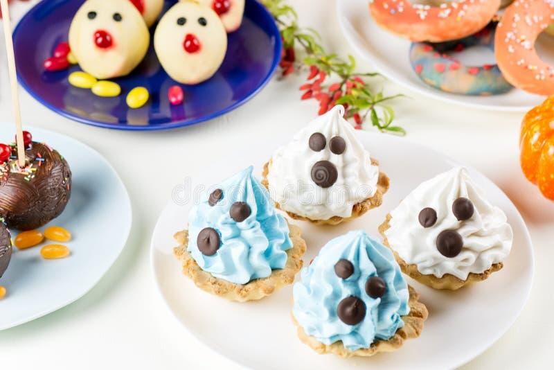 Halloweenowe cukierki fundy, partyjny karmowy pojęcie Biel i błękitni torty z twarzami zamykamy up zdjęcia royalty free