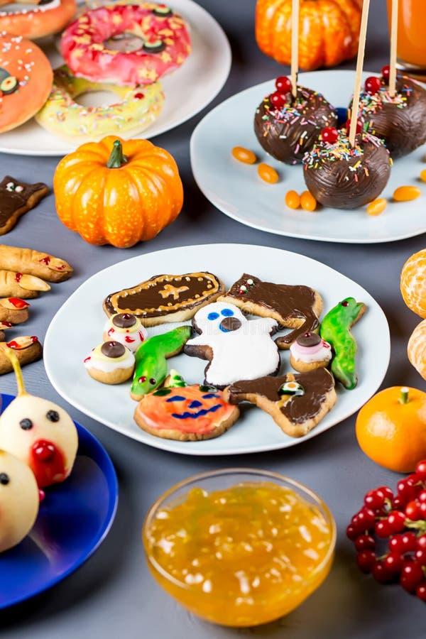 Halloweenowe cukierki fundy, partyjny karmowy pojęcie Straszni ciastka, potworów ciastka i owoc na popielatym tle, zdjęcie stock