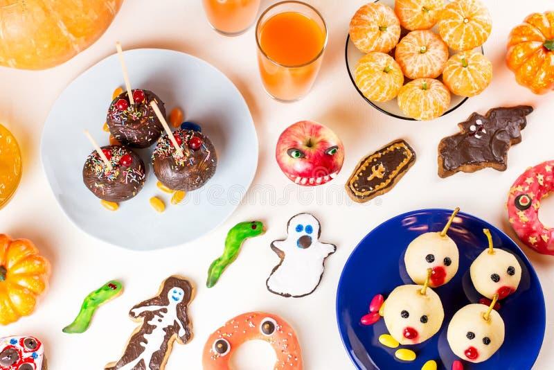 Halloweenowe cukierki fundy, partyjny karmowy pojęcie Straszni ciastka, potworów ciastka i owoc na popielatym tle, zdjęcia royalty free