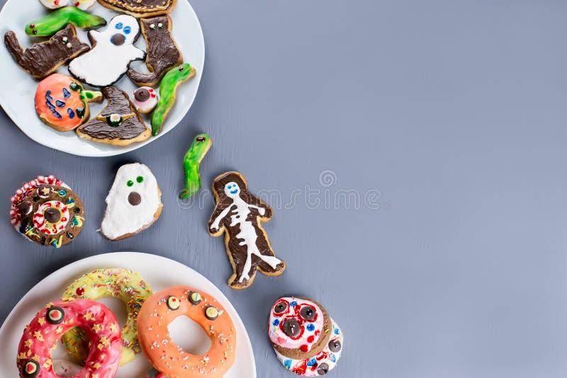 Halloweenowe cukierki fundy, partyjny karmowy pojęcie Straszni ciastka, potworów ciastka i owoc na popielatym tle, zdjęcie royalty free
