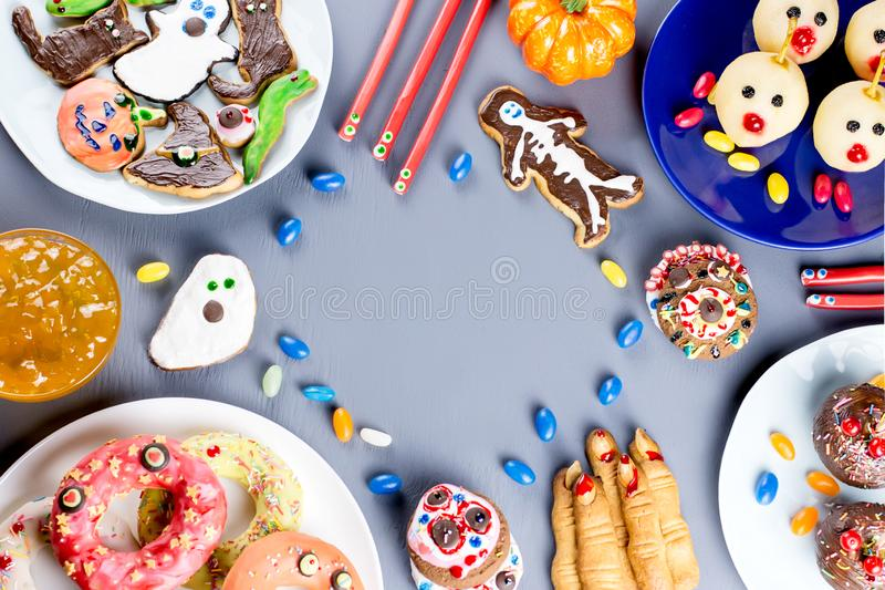 Halloweenowe cukierki fundy, partyjny karmowy pojęcie Straszni ciastka, potworów ciastka i owoc na popielatym tle, zdjęcia stock