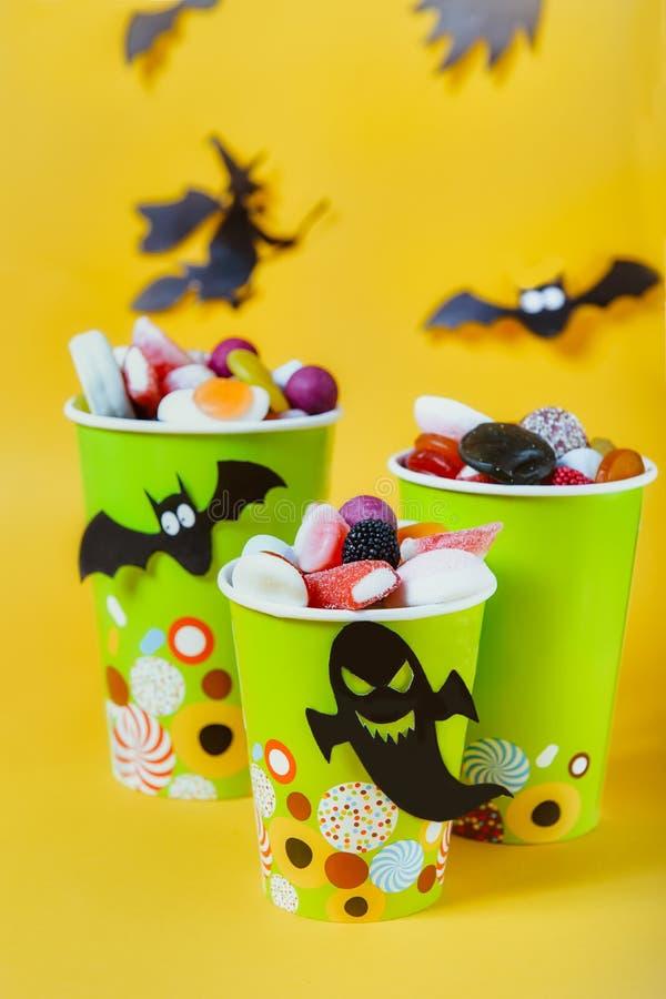 Halloweenowi trikowi lub funda cukierki Papierowe filiżanki z colourful cukierkami wśrodku i papierowymi sylwetkami nietoperze, d zdjęcie stock