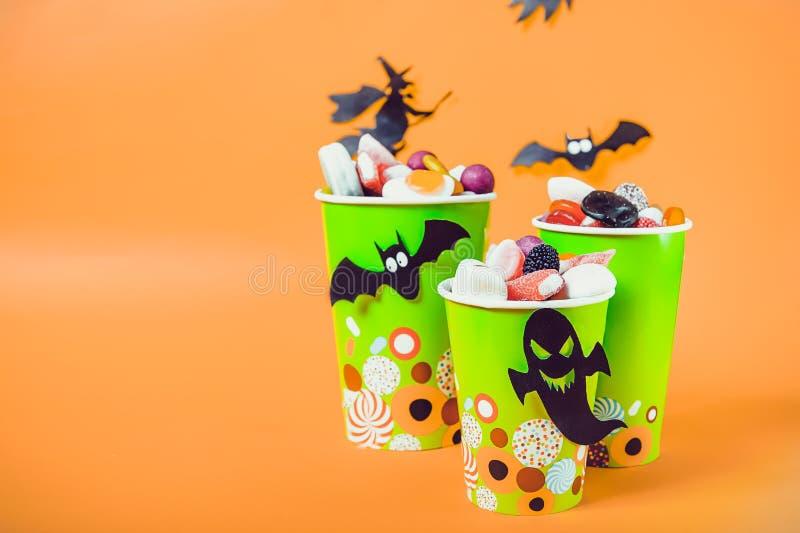 Halloweenowi trikowi lub funda cukierki Papierowe filiżanki z colourful cukierkami wśrodku i papierowymi sylwetkami nietoperze, d fotografia stock