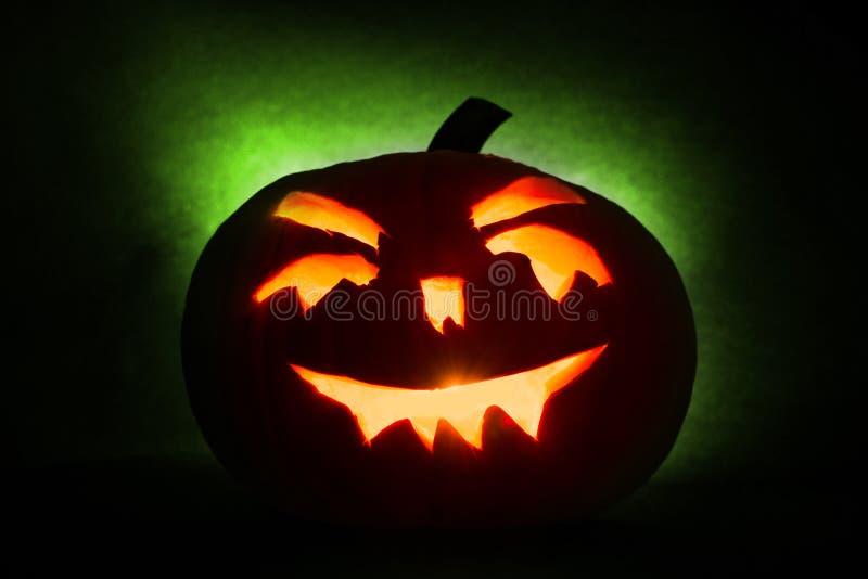 Halloweenowy bani głowy dźwigarki lampion z płonącymi świeczkami na zielonym tle zdjęcia stock