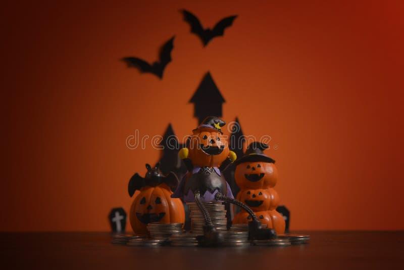 Halloweenowy bania lampion z pieniądze monety sterty narastającym biznesem na pomarańczowym tle obrazy stock