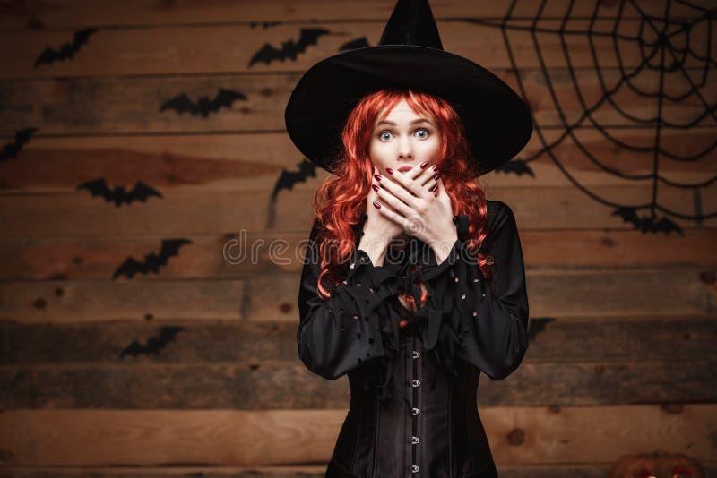 Halloweenowy czarownicy pojęcie - Szczęśliwy Halloweenowy czerwony włosiany czarownicy mienie pozuje z szokującą twarzą nad stary obrazy stock