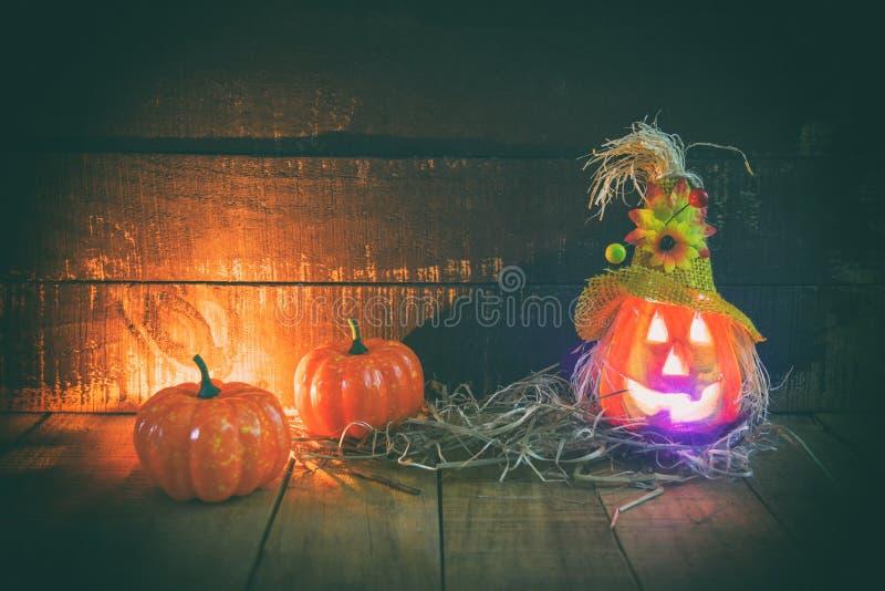 Halloweenowy dyniowy lampion z suchą słomą na drewnianym - kierowniczych dźwigarki o latarniowych złych twarzy straszny wakacje d zdjęcia royalty free