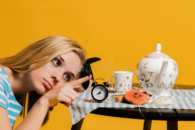 Halloweenowy dziewczyny pojęcie, psychodeliczny spojrzenie, Alice w krainie cudów z herbatą i zegarem obrazy stock