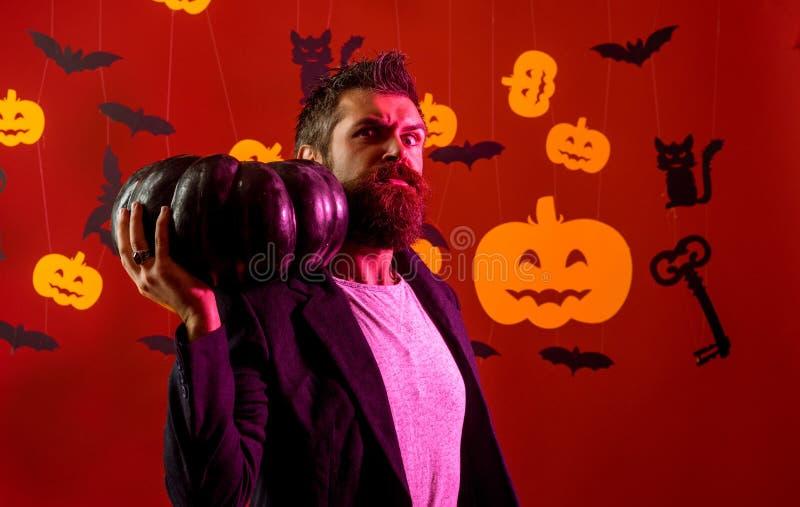Halloweenowy m??czyzna z bani? w ciemno?ci Z?y witcher z czerwonym w?osy i broda w czarnej pelerynie czyta ksi??k? czary zdjęcie royalty free