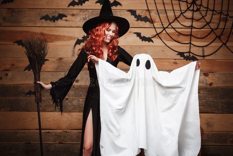 Halloweenowy pojęcie czarownicy matka i mały biały duch robi - trikowemu lub fundzie z wyginającym się bani ove świętuje Hallowee zdjęcie stock