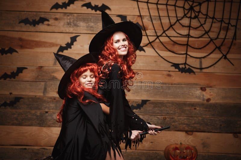 Halloweenowy pojęcie Piękny caucasian macierzysty i jej córka lata z magicznym broomstick z długim czerwonym włosy w czarownica k obrazy royalty free