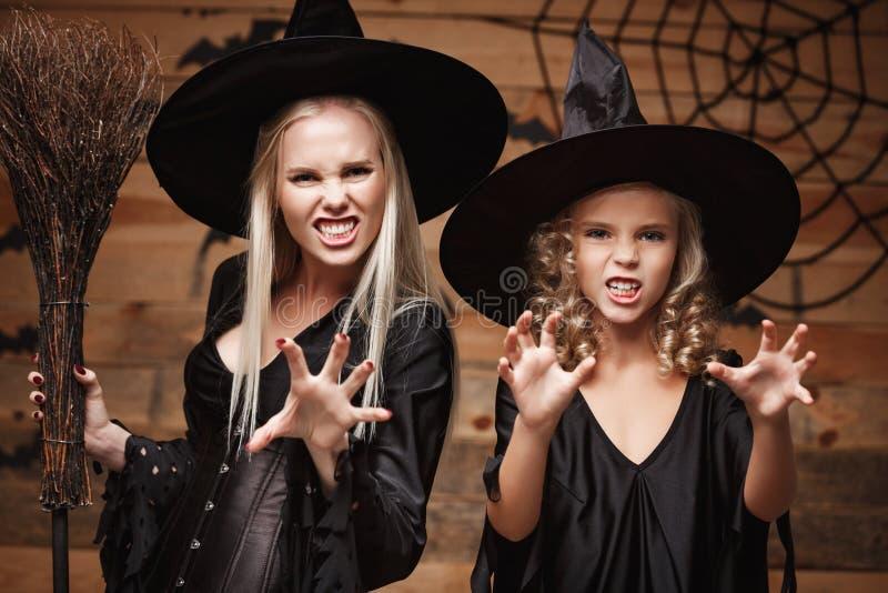 Halloweenowy pojęcie zbliżenia piękny caucasian macierzysty i jej córka świętuje Halloween pozuje z wyginający się w czarownica k zdjęcia stock