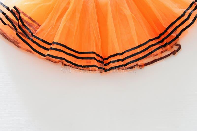 Halloweenowy wakacyjny minimalny odgórnego widoku wizerunek pomarańczowy tiul spódnicy kostium nad białym drewnianym tłem kosmos  obrazy royalty free