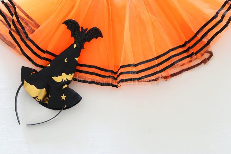 Halloweenowy wakacyjny minimalny odgórnego widoku wizerunek pomarańczowy tiul spódnicy kostium nad białym drewnianym tłem kosmos  zdjęcia stock