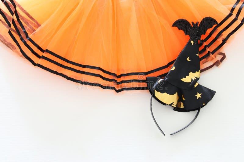 Halloweenowy wakacyjny minimalny odgórnego widoku wizerunek pomarańczowy tiul spódnicy kostium nad białym drewnianym tłem kosmos  fotografia royalty free