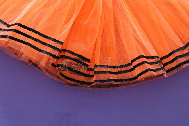 Halloweenowy wakacyjny minimalny odgórnego widoku wizerunek pomarańczowy tiul spódnicy kostium nad purpurowym drewnianym tłem kos obrazy royalty free