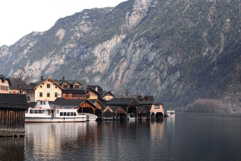 Hallstatt老镇村庄看法,议院和小船靠码头 免版税库存照片