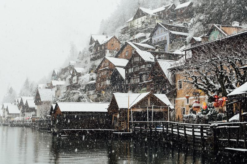 HALLSTATT,奥地利- 2018年12月:在老镇木房子的看法在雪风暴期间的 免版税图库摄影