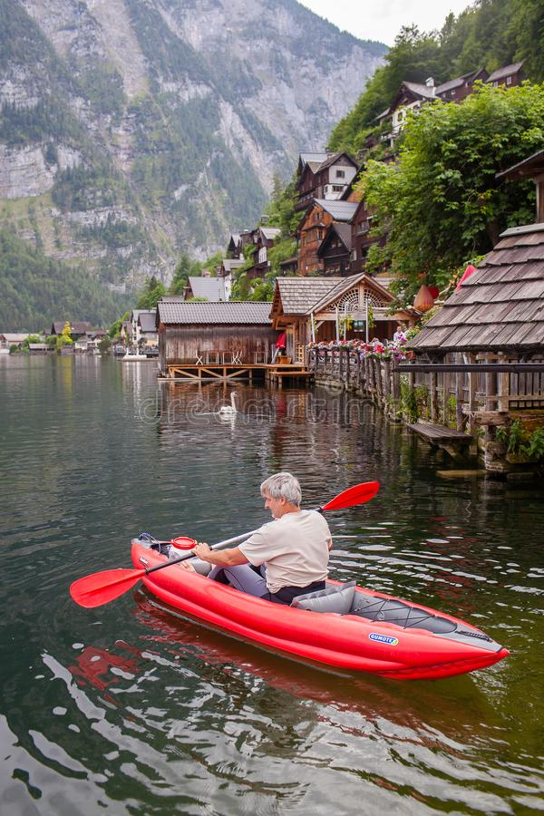 Hallstatt, Austria - 31 de mayo de 2018: Un hombre está flotando en una canoa en un lago foto de archivo libre de regalías