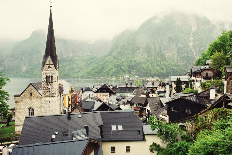 Hallstatt, Austria village, church and Alpine foggy lake, rooftops of wooden houses royalty free stock photos