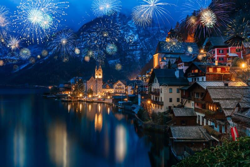 Hallstatt en Austria que celebra Noche Vieja con el fuego artificial colorido que destella foto de archivo